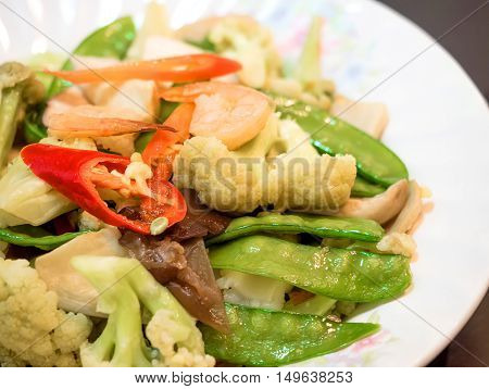 Healthy food delivery. Fitness food. Weight loss nutrition diet. Eat right concept, healthy food, clean food on dish, Sautéed mixed vegetables in oyster sauce with fresh shrimp.