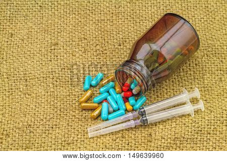 colorful pills bottle tablets syringes and needle lie strewn on brown sack fabric background