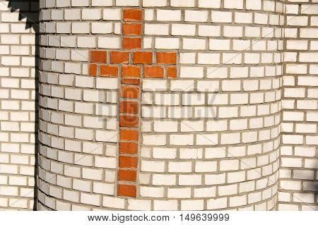 Cross from orange bricks on white wall of small chapel.
