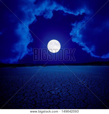 supermoon in clouds over desert