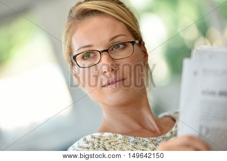 Middle-aged blond woman with eyeglasses reading newspaper