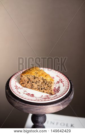 Piece of freshly baked banana cake with walnuts on a dessert plate on a cake stand, selective focus