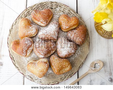 closeup of a heart shaped donuts with powdered sugar