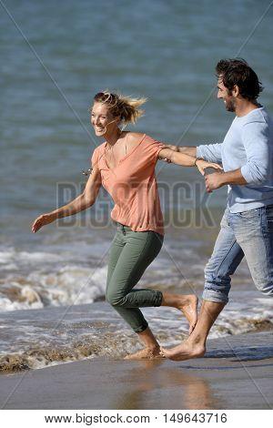 Couple running and having fun on the beach