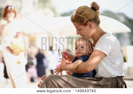 OSTROG MONASTERY, MONTENEGRO - JULY 21, 2016: a young mother takes care of her baby feeding him