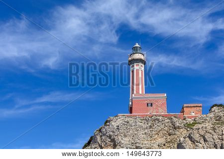 Lighthouse On A Cliff In Day Time. Horizontal Image With Red And White Lighthouse On A Cliff In Summ