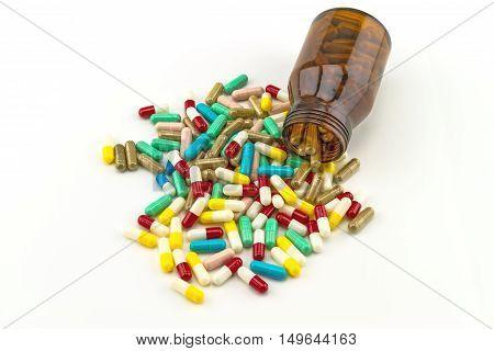 Colorful tablets medicine in black bottle on white background