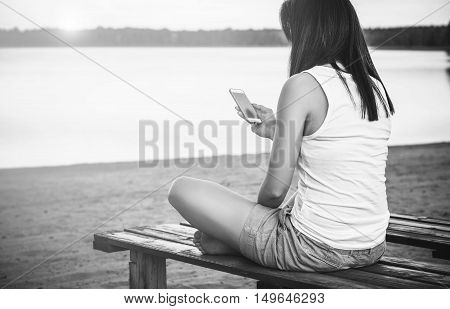 Girl Relaxing On The Beach With Phone