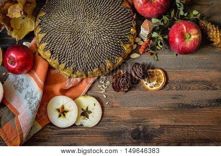 Rural vintage autumn red apples, sunflower, pine cones, orange and apple slices on a rustic wooden background, natural fall style decorations. Natural plenteous border background vintage mock up.