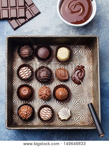 Chocolate candies in a vintage baking dish with chocolatier tool