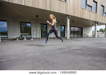 Full length side view of determined young woman running by building
