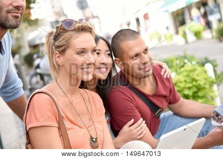 Friends on vacation looking at tourist information on tablet