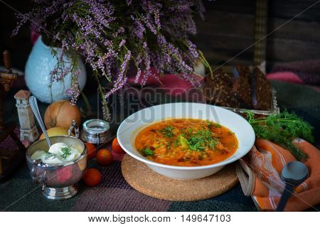 Traditional ukrainian vegetable soup with sour cream and rye bread. National cuisine. Borscht. Soup with tomato, carrot, onion and potato. Rustic food background