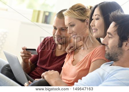 Group of friends using laptop and buying online, e-shopping