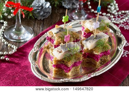 Holiday Appetizer: Canapes In The Form Of A Star With Pickled Herring, Beetroot Dip And Dill On A Fe