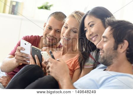 Friends at home playing with smartphones, connecting people