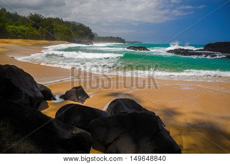 black lava rocks golden sands aquamarine waters and a green lush shoreline make lumahai beach on kauais north shore one of the most beautiful in all of the hawaiin islands.
