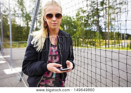 Portrait of sporty young woman holding mobile phone while listening music by fence