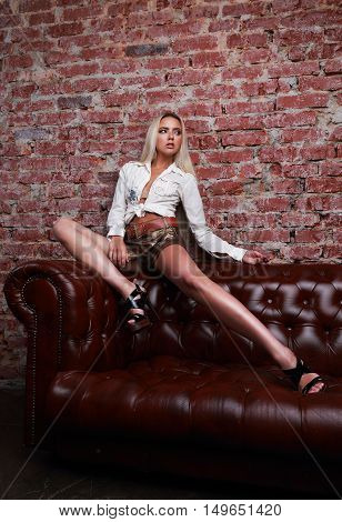 Sexy Female Model Posing On The Sofa In White Shirt And Leather Shorts And High Heels On Bricks Wall