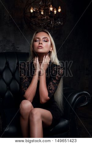 Beautiful Blond Mystical Woman Spelling Sitting On Black Armchair On Candle Light Background