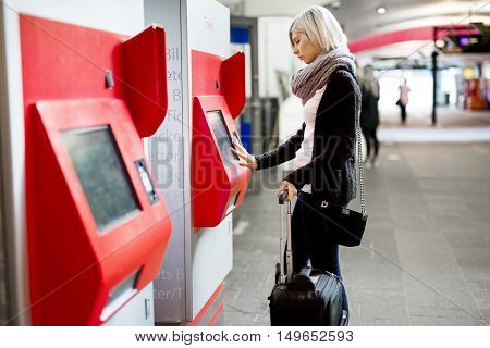 Side view of young woman with luggage buying train ticket using vending machine at station