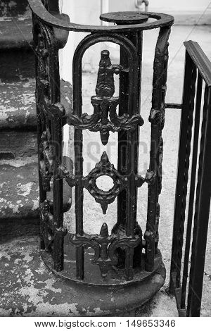 A closeup of details on the wrought iron work on a stair railing.