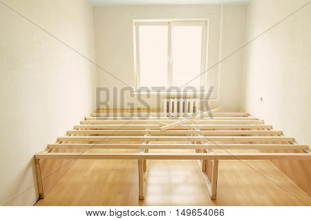 light room under renovation with white walls and wooden floor
