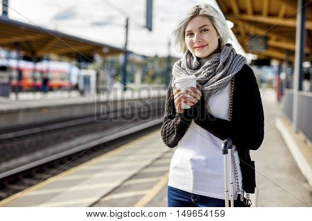 Portrait of young woman holding disposable coffee cup on platform at train station