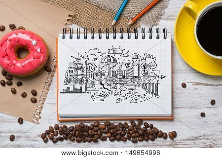Top view of wooden table and notepad with sketches