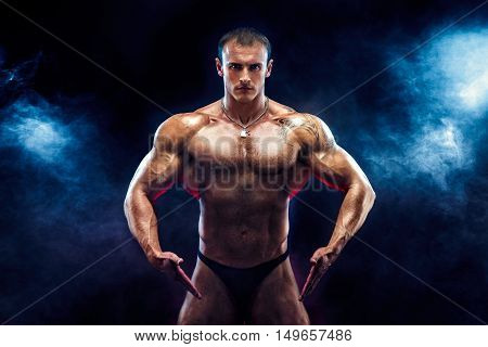 Close up on perfect abs. Strong bodybuilder with six pack.Strong bodybuilder man with perfect abs, shoulders, biceps, triceps and chest, personal fitness trainer flexing his muscles in blue, red smoke