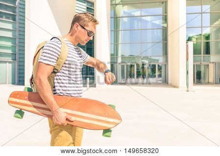 Handsome hipster guy looking at his watch for the next date. Man checking time for meeting with backpack and longboard on city town background. Active person in everyday life moments.