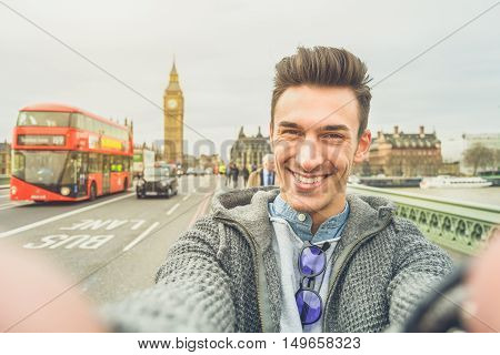 Smiling guy take selfie photo during travel in London England. Traveler man in front of Big Ben Tower taking memory pic with iconic england red bus. Happy people concept wandering around the world.