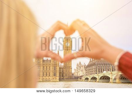 Girl traveling show love for London city making heart with her fingers on Big Ben Tower. Emotional concept of happy exclusive lifestyle moment sharing time discovering new place. Travel photography.