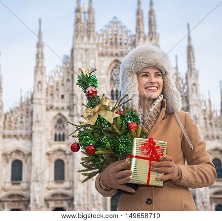 Woman With Christmas Tree And Gift Looking Into Distance, Milan