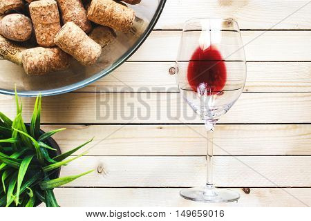 Glass with red wine on a light wooden table