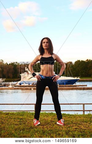 Athletic body and legs of sport girl in the park near river. Cpy space for advertising. Girl in fitness dark wear training legs before or after run.