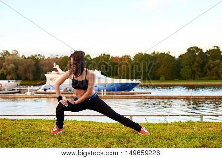 Beautiful brunette girl doing stretching exercises on legs before or after running in tne summer or autumn evening. Woman with sport and athletic body keep health lifestyle.