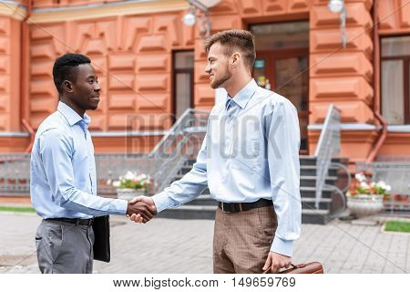 African American businessman and a Caucasian businessman shaking hands on the background red buildings in the city