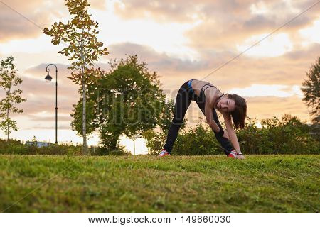 Workout fitness outdoors. Healthy lifestyle with body training. Prepairing to hard run in the street. Fresh air sport concept in sunset evening time.