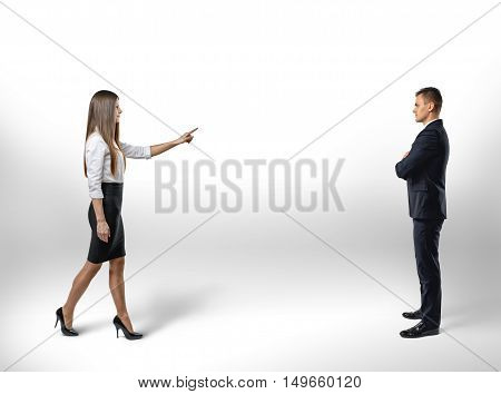 Businesswoman pointing a finger takes a step toward to businessman. Make the first move. Select. The relationship between colleagues.