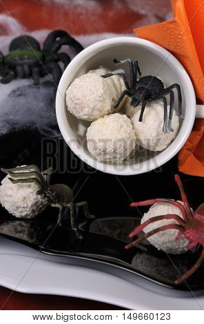 Candies in the form of spider eggs in a cup on the table in Halloween