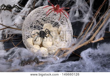 candy in the form of spider eggs in a cocoon with a spider on the table for Halloween