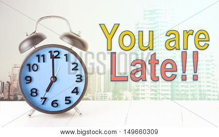 you are late text with blue alarm clock city background