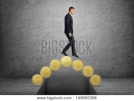 Businessman crossing a bridge made of golden coins. Earning money. Making a fortune. Man of wealth. Growing prosperity.