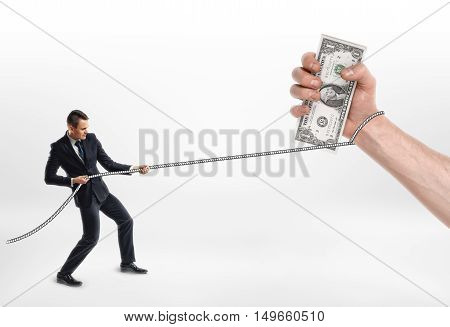 Businessman grabbed a big hand with cash dollars and pulls it by rope. Loans and credit. Income tax. Duty.