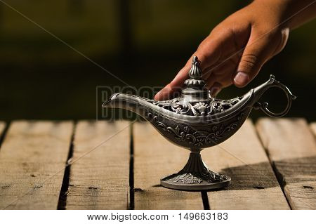 Beautiful antique metal lamp in true Aladin style, hand touching it gently, sitting on wooden surface.