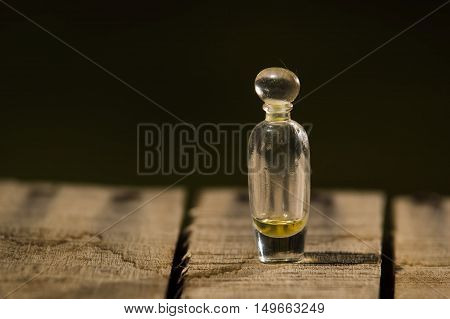 Closeup small glass bottle for magicians with tiny amount of remedy inside, standing on wooden surface.