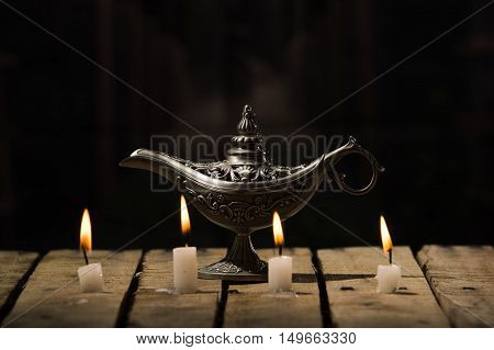 Four white wax candles sitting on wooden surface burning, Aladin style lamp placed behind, black background.