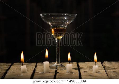 Four white wax candles sitting on wooden surface burning, cocktail glass placed behind, black background.