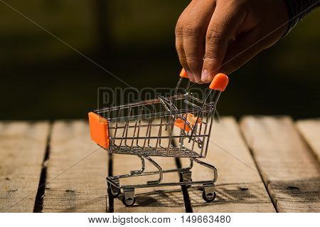 Miniature shopping trolley sitting on wooden surface, big hands touching handle, magicians concept.